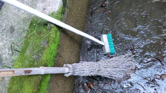 デッキブラシと竹箒で掃除