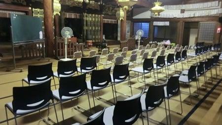 寺の法要準備のため椅子を並べる